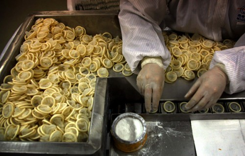 A worker places condoms onto a packaging belt at the Chinese condom manufacturer Safedom's factory